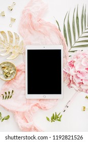 Modern home office desk workspace with blank screen tablet, pink hydrangea flowers bouquet, tropical palm leaf, pastel blanket, monstera leaf plate and accessories on white backgroun. Flat lay