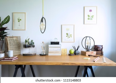 Modern home office interior with wooden desk, books,poster illustrations of plants, table lamp and office accessories. Stylish creative and vintage desk.