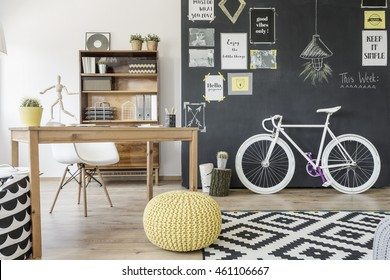 Modern home space with chalkboard wall, bike, pouffe, pattern carpet, desk and chair