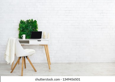 Modern home working place with laptop, and house plants at white brick wall background, copy space