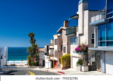 Modern homes lining a street near Manhattan Beach California on a sunny blue sky day.