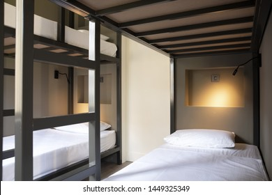 Modern hostel, hotel, dorm, dormitory interior view on wooden floor. Beds in the spacious room. Guest house concept for travelers. Accomodation for tourists. Clean and cozy rest place.