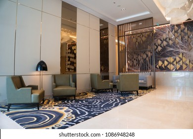 Modern hotel lounge with mirrors and white glossy floor. Comfortable grey sofa, armchairs and floor lamp placed on blue patterned carpet. Panoramic window curtained with dark blinds.