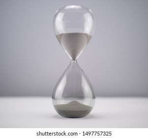 Modern Hourglass with blurry window-view background -- sand trickling through the bulbs of a crystal sand glass. every second counts. symbol of time. countdown