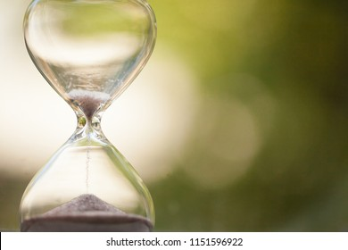 Modern Hourglass with green background -- sand trickling through the bulbs of a crystal sand glass, time is running out. every second counts. symbol of time. countdown.