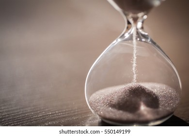 Modern hourglass on wooden background with copy space. Hourglass time passing concept for business deadline, urgency and running out of time