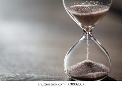 Modern hourglass on wooden background with copy space. Hourglass time passing concept for business deadline, urgency and running out of time.