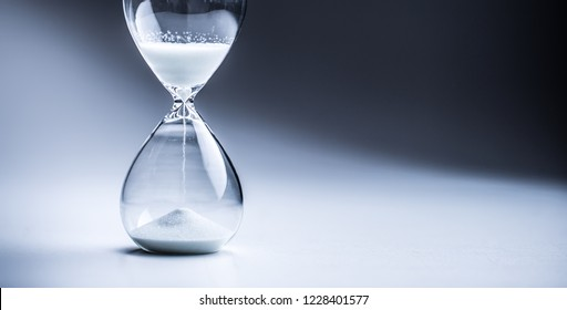 Modern hourglass in running time in studio lights.