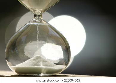 Modern Hourglass -- sand trickling through the bulbs of a crystal sand glass. every second counts. symbol of time. countdown. Sand clock.