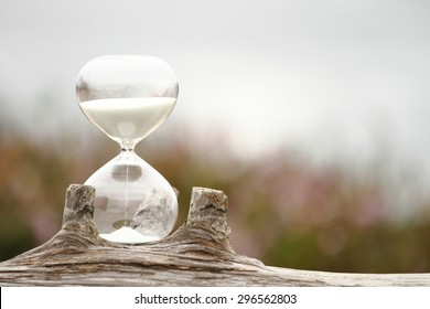 Modern Hourglass -- sand trickling through the bulbs of a crystal sand glass. every second counts. symbol of time. countdown. Time Management.