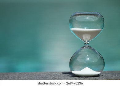 Modern hourglass sits on poolside -- sand trickling through the bulbs of a crystal sand glass. every second counts. symbol of time. summer countdown.