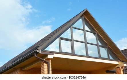 Modern house attic construction with roof guttering and panoramic mansard, attic skylight window.