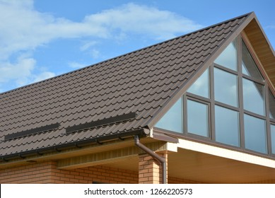 Modern house attic  metal tile roof with panoramic glass wall window and roof gutter.