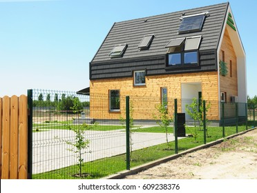 Modern House Building with energy saving and energy efficiency. Eco-house or eco-home. Roofing Construction with attic window skylights, solar panels and solar water heater (SWH) system. Passive House