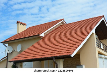 Modern house with chimney, red clay tiled roof, rain gutter and gable and valley type of roof construction. Roofing Construction.