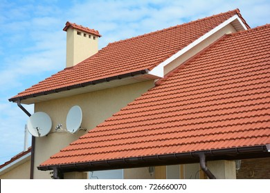 Modern house with chimney, red clay tiled roof and gable and valley type of roof construction. Building attic house construction with different types of roof designs.Roofing Construction.