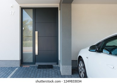 Modern house entrance with parking car next to it