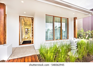 Modern house entrance with wooden door and concrete floor with a grass on the ground