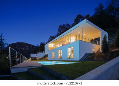 Modern house, exterior in the night, lights on