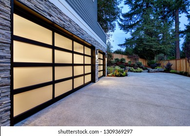 Modern house exterior with two car garage, spacious driveway at twilight