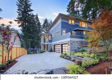 Modern house exterior with two car garage, spacious driveway and nice landscape