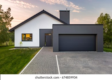 Modern house with garage and green lawn, exterior view
