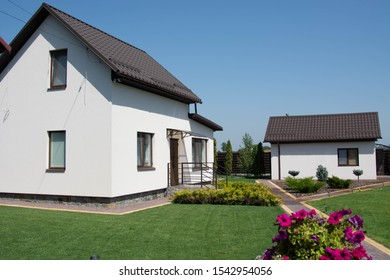 Modern house with green lawn, playground and trampoline. exterior view