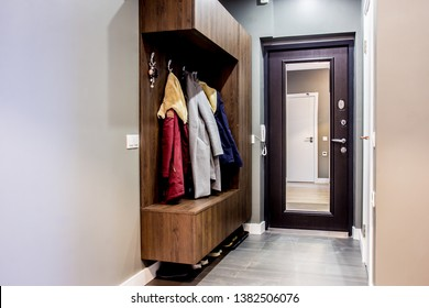 Modern house interior hallway decor elements with front door and segments of luxury furnishing empty apartment with wooden wardrobe and clothes