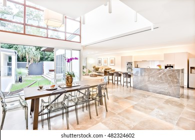 Modern house interior and outdoor including dining and kitchen beside living room, the dining or patio area has a wooden table with plastic see through chairs on the tile floor,  the house illuminated
