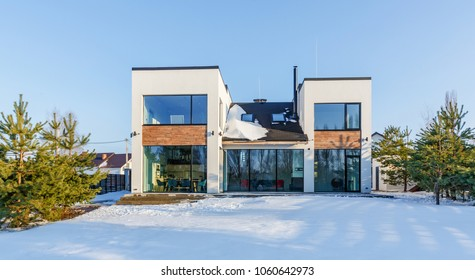 A modern house with large panoramic windows in the background of a snow-covered landscape.
