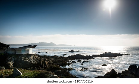 Modern house next to the coastline of the pacific ocean and the sun shining on the surface of the water during summer, Carmel Highlands, California, West Coast, USA