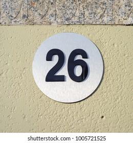 Modern house number twenty six (26) on a metal plate