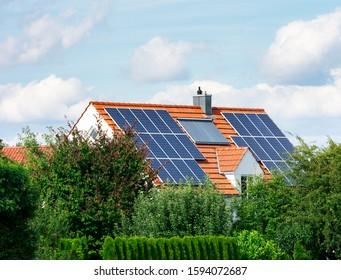 Modernes Haus mit Fotovoltaik-Solarzellen auf dem Dach und einer thermischen Solaranlage für alternative Energieerzeugung