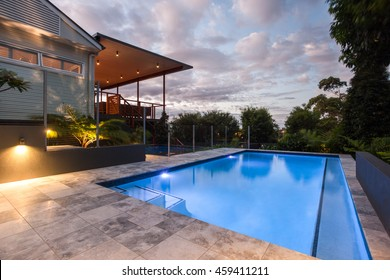 Modern house with a pool at evening or in the morning, which illuminated with yellow lights on the wall and surrounded by green trees, forest under blue sky with white clouds