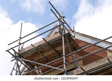 Modern house roof construction with scaffold pole platform. New build domestic building against blue sky with clouds