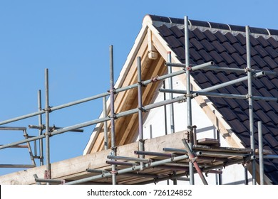 Modern house roof construction with scaffold pole platform. New build domestic building.