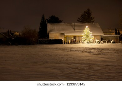 A modern house with a tall christmas tree and a lot of fresh snow at night in Lachen, Neustadt an der Weinstrasse, Germany.