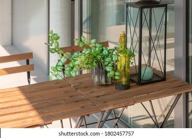 La moderna terraza de la casa con mesa y sillas de madera. Una plántula, una botella y una linterna sobre la mesa. Día soleado en verano.