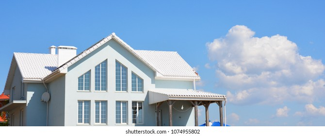 Modern house with white roof tiles for energy saving panorama.  White roof bring cool savings and can reduce air conditioning costs by up to 20 percent.