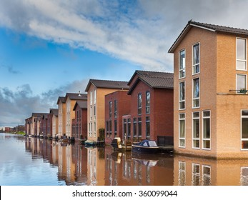 Modern Houses on the Water Front in a row with jetty and boats
