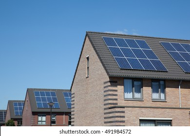 Modern houses with solar panels on the roof for alternative energy.