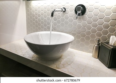 Modern hygienic wash basin with running clean water from tap faucet