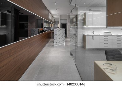 Modern illuminated interior of a dental clinic with light and textured brown walls and tiled gray floor. There is a reception desk, doors, cabinet with glass partition, table, lockers with a sink.