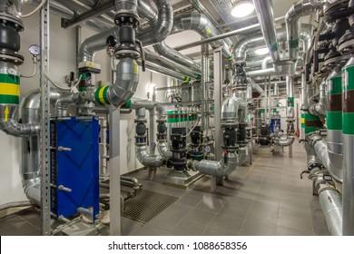 Modernes unabhängiges Heizsystem im Kesselraum. Rohrleitungen, Wasserpumpe, Ventile, Wärmetauscher.