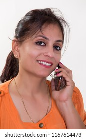 Modern Indian homemaker lady wearing an orange colored shirt talking or chatting with a friend over a mobile or cellphone