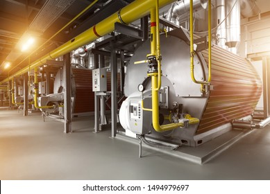 Modern industrial gas boiler room equiped for heating process. Heating gas boilers, pipelines, valves. Sun flares