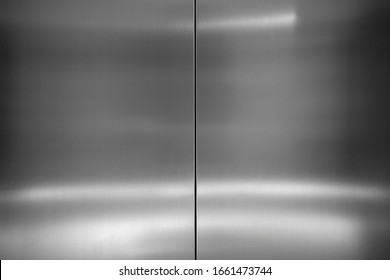 Modern industrial metallic background. Close up photograph of elevator doors stainless steel surface texture with shiny bright light reflected on surface