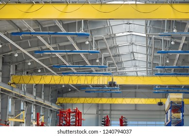 A modern industrial workshop, three overhead cranes under the ceiling.