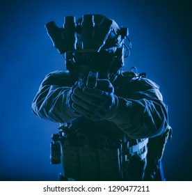 Modern infantry soldier, special forces fighter, police SWAT officer in helmet and body armor, equipped night vision device, aiming with service pistol in camera, front view, low key studio shoot