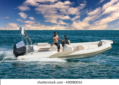 Modern Inflatable Rubber Speed Motor Boat on water with man on steering wheel